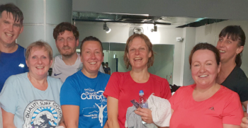 A group of sweaty, happy people pose for a photograph after completing a spinning class at the gym